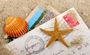 postcards in the sand with seashells
